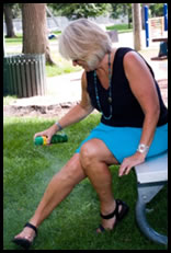 woman spraying her legs with deet